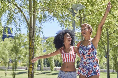 Girlfriends walking in park - PGCF00104