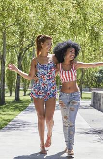 Girlfriends walking in park - PGCF00107