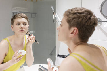 Beautiful woman with short hair applying make-up while looking at her reflection on mirror in bathroom - TAMF02487