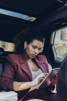 Young female professional using digital tablet while sitting in car - MTBF00558