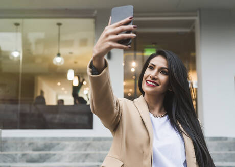 Woman taking a selfie with her smartphone in city - DSIF00023