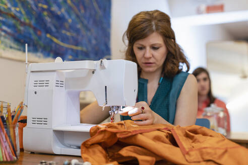 Female seamstress sewing orange fabric on machine at fashion studio - EIF00101