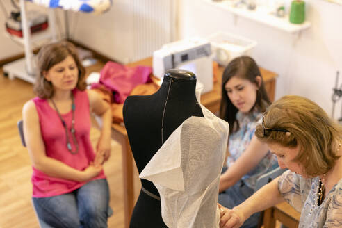 Female professionals looking at senior designer working on mannequin in studio - EIF00107