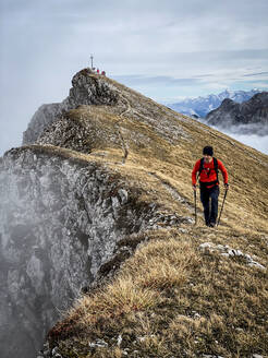 Man hiking with poles on mountain peak during foggy weather - MALF00016