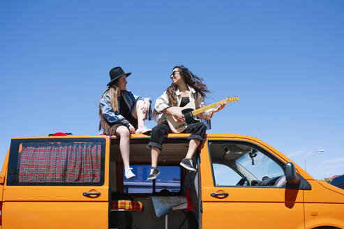 Two women sitting on roof of van, playing guitar - JCMF00983