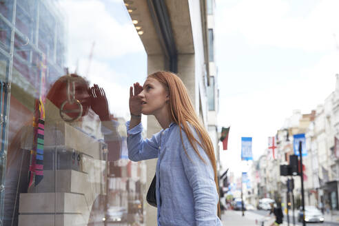 Redhead woman shielding eyes while looking through store window in city - PMF01156