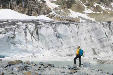 Mature male hiker looking at melting glacier - MCVF00503