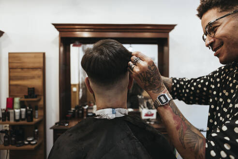 Barcelona, Spain - Barber working a haircut on a client in his barbershop - XLGF00368