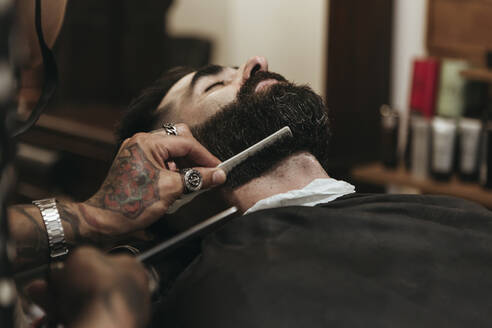 Barber combing client's beard at salon - XLGF00377