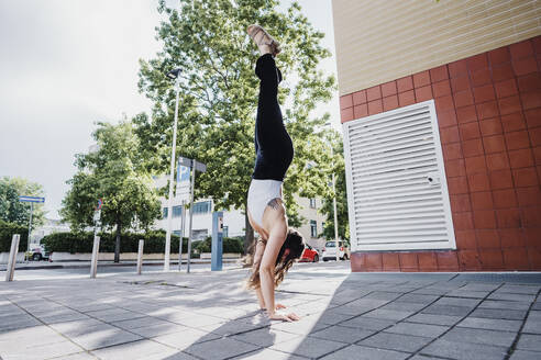 Young woman performing handstand in city during sunny day - MEUF01299