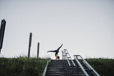 Young woman performing handstand on steps against clear sky - MEUF01323