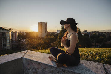 Relaxed woman using VR glasses while performing yoga in prayer positon on retaining wall in city - MEUF01332