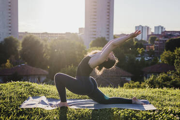 Young woman practicing yoga in warrior position at city park during sunny day - MEUF01341