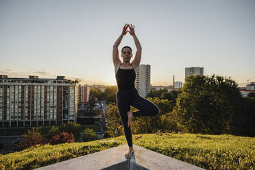 Young woman practicing yoga in tree pose on retaining wall in city during sunset - MEUF01347