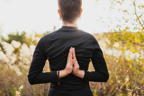Woman practicing reverse prayer position while standing outdoors - MRRF00123