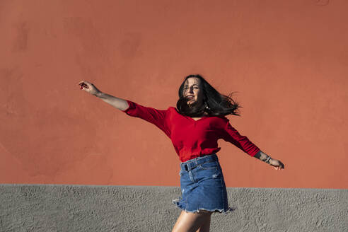 Carefree young woman dancing against orange wall in city on sunny day - MCVF00521