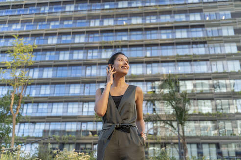 Smiling businesswoman talking over wireless earphone while standing against building in city - AFVF06723