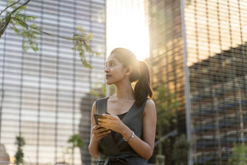 Thoughtful businesswoman holding smart phone while standing against modern buildings - AFVF06729