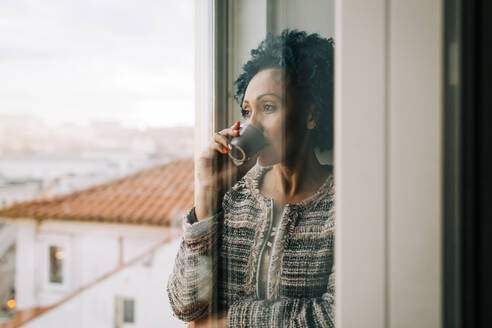 Woman drinking coffee while looking through window at home seen through glass door - DCRF00392