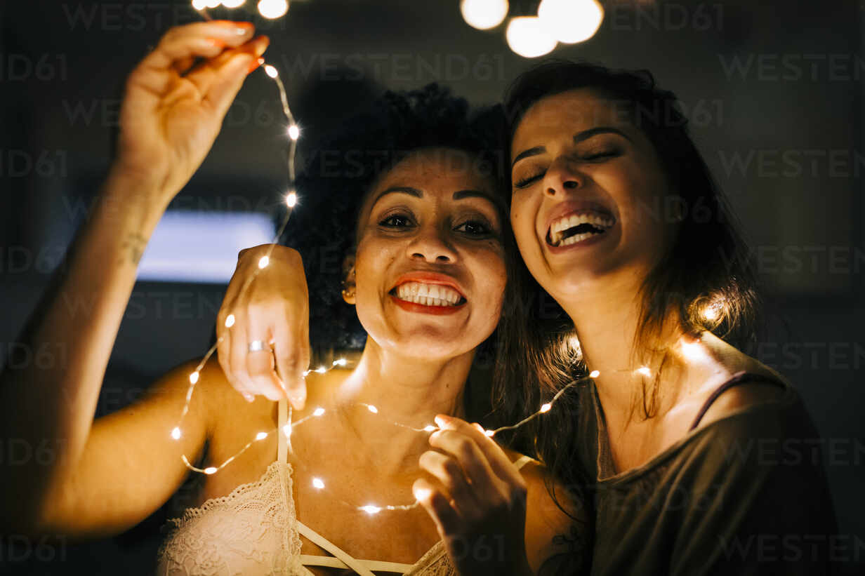 Close-up of cheerful female friends holding illuminated string lights at home - DCRF00398 - Alexandra C. Ribeiro/Westend61