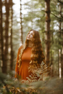 Thoughtful beautiful woman with long hair standing in forest - TCEF00936