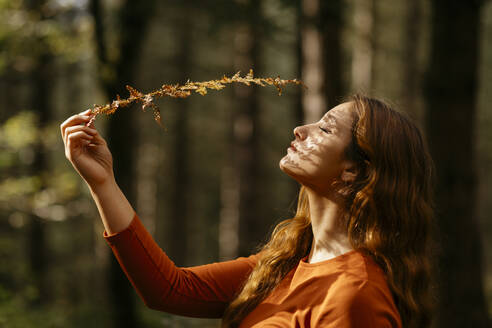 Close-up of beautiful woman with eyes closed holding plant in forest - TCEF00942