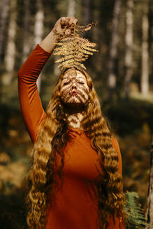 Beautiful woman with long hair holding leaves while standing in forest - TCEF00945