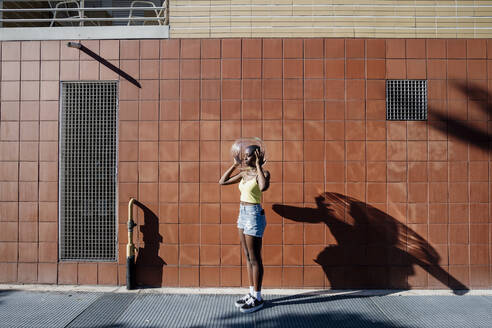 Young woman holding glass container over head while standing over sidewalk in city - MEUF01351