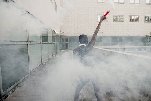 Young woman holding smoke bomb while standing on footpath against building - MEUF01426