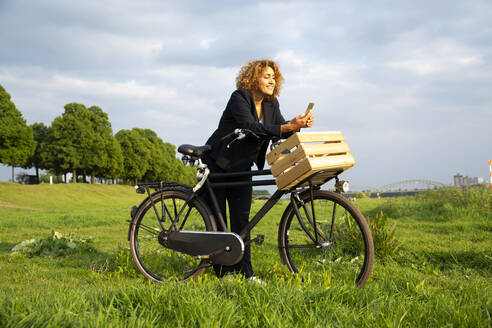 Businesswoman using smart phone while standing with bicycle on grassy land against sky - MJFKF00511