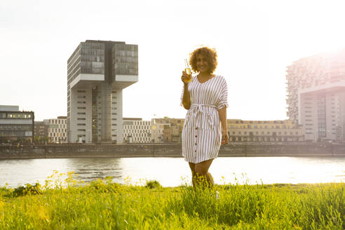 Smiling woman holding beer bottle while standing on grassy land against river in city at sunset - MJFKF00514