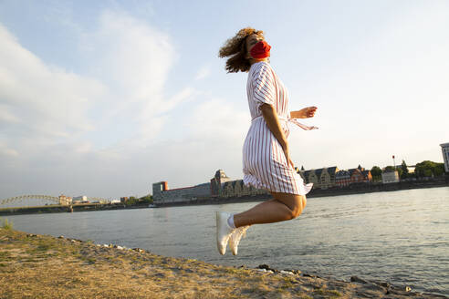 Mid adult woman wearing mask jumping at riverbank against sky in city - MJFKF00526