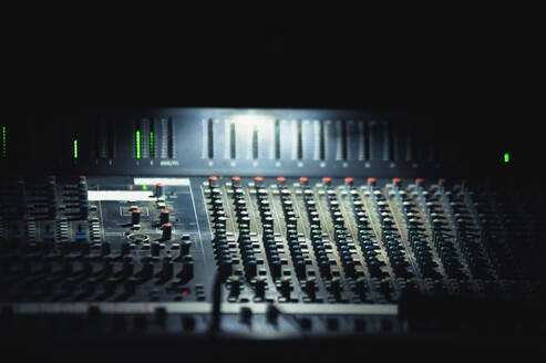 Spot of bright light illuminating profession mixing panel during show - ADSF01254