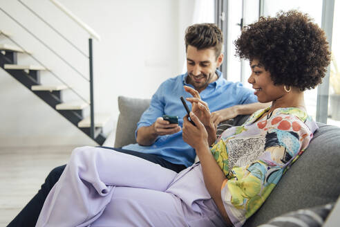 Couple using smart phones while sitting on sofa in modern penthouse - EHF00563