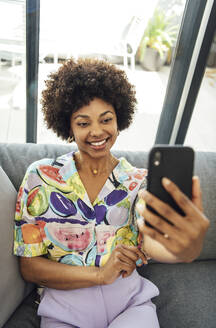 Happy woman taking selfie through smart phone while sitting on sofa in penthouse - EHF00566