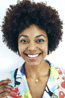Happy woman with afro hairstyle against white background - EHF00578