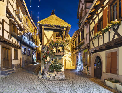 Half-timbered houses along Rue du Rempart Sud lit up with Christmas decorations at night, Eguisheim, Alsace, France, Europe - RHPLF16143