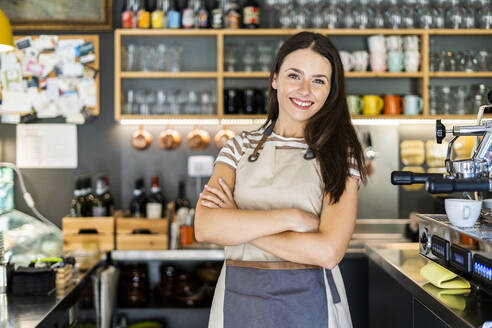 Happy female owner standing arms crossed in coffee shop - GIOF08561