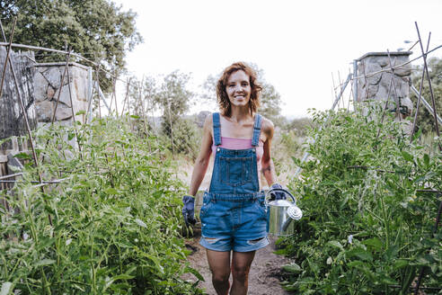 Smiling woman holding watering can while standing amidst plants in vegetable garden - EBBF00449