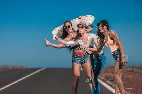 Cheerful attractive multiethnic friends with long boards showing thumb ups for trying to stop car on asphalt route and blue sky in Lanzarote, Canary Island, Spain - ADSF01545