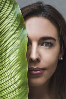 Close-up portrait of beautiful woman with leaf - DSIF00046
