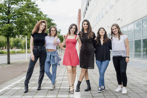 Smiling female friends posing while standing on footpath in city - MEUF01502