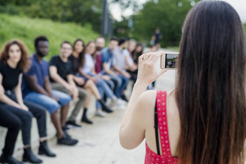 Woman photographing friends sitting in row with smart phone at park - MEUF01520