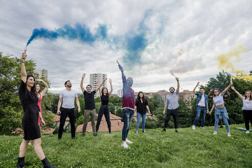 Cheerful group of friends playing with smoke bombs in park against cloudy sky - MEUF01535