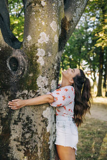 Cheerful young woman with long hair embracing tree trunk while standing in park - DCRF00479