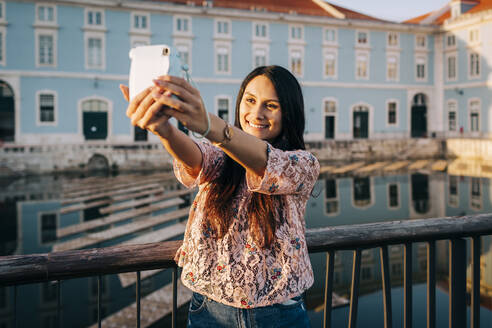 Young woman taking selfie through camera while standing on bridge - DCRF00500