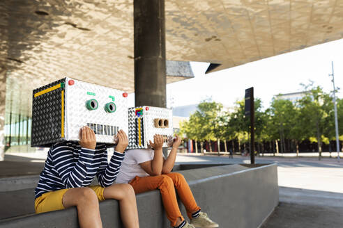 Friends wearing robot costumes sitting on retaining wall in city - VABF03125