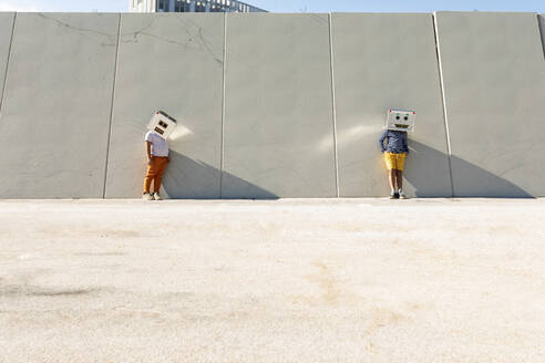 Friends wearing robot masks standing against wall in city on sunny day - VABF03131