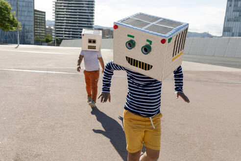 Carefree boy wearing robot mask dancing while friend walking on street in city - VABF03134