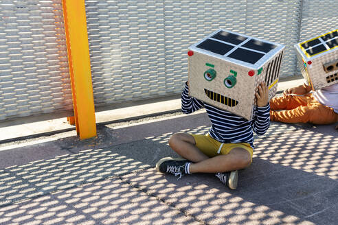 Boys wearing robot masks made of boxes sitting on road by fence in city - VABF03137